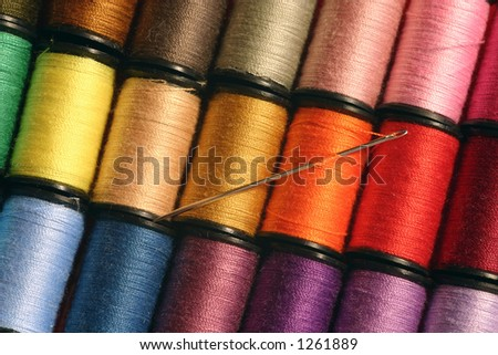 A needle at rest among colorful sewing threads. - stock photo