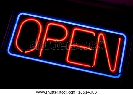 A neon OPEN sign glowing red in the window of a restaurant. - stock photo
