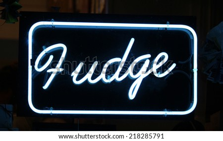 A neon sign reading Fudge against a black background