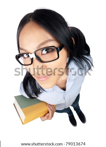 A nerdy Asian girl holding a book and looking into the camera shot with a wide angle lens