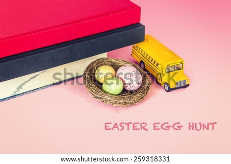 A nest of colorful eggs with a model of school bus and books. Symbolic concept of easter egg hunt, children education. Instagram filtered look. Copy Space.  - stock photo