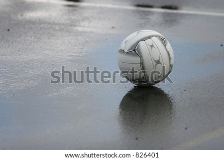 A Netball ball sitting on the court during the half-time break on a rainy day.  Focus is on ball, DOF isn't all that large. - stock photo