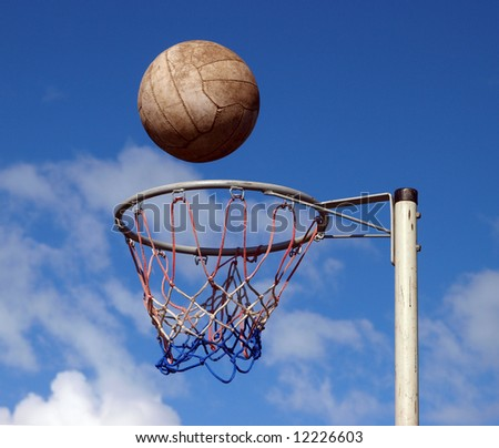 A netball frozen mid air above the goal - stock photo