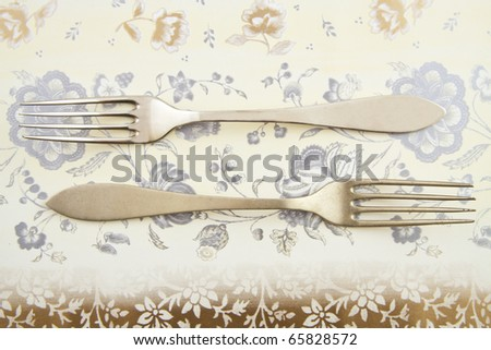 A new and an old fork on a vintage background - stock photo