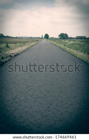 A new asphalt road between the meadows with a vintage look and a farm at the end of the road - stock photo