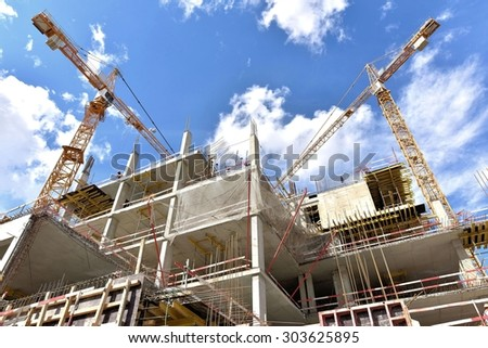 A new building is being constructed with use of tower crane. - stock photo