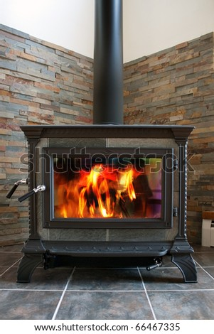 A new cast iron wood stove burning hot with slate tile. - stock photo