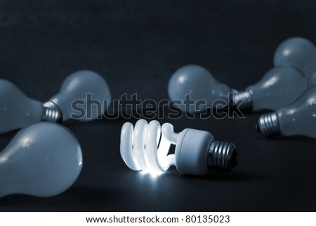 A new energy efficient CFL light bulb shines while the old ones fade into darkness. - stock photo
