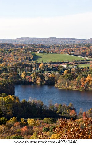A New England countryside landscape with early autumn foliage at its peak colors.