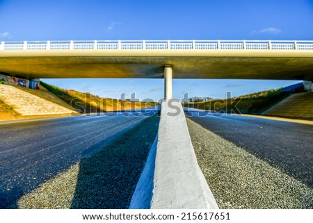 A new highway with security barrier closeup under modern new bridge - stock photo