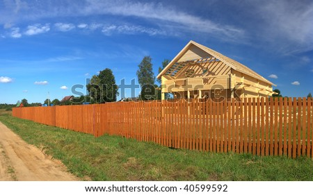 A new home being built with wood behind a brown fence (Panorama)