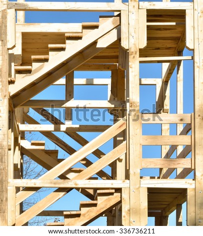 A new house is under construction on a piece of property. The sky is clear and blue, and the home is being built with wood trusses and planks. - stock photo