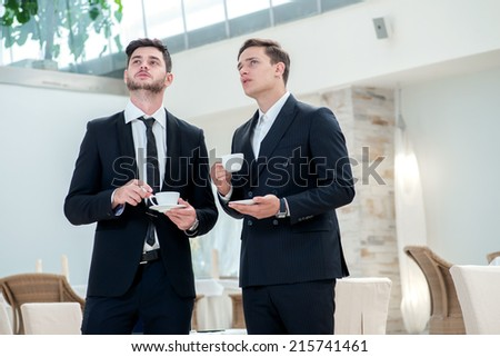 A new idea. Two other businessman drinking coffee and talking to each other while standing in an office and smiling to each other