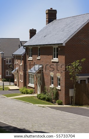 A new modern housing development. A row of recently built new houses constructed of red brick with grey slate roofing. location in Salisbury, Wiltshire.