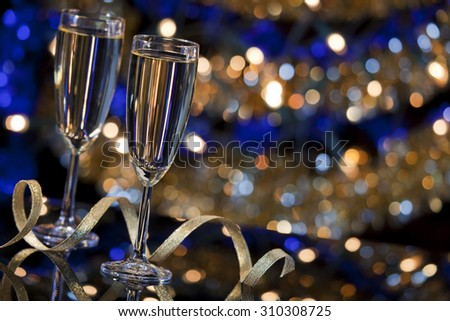 A New Year's Eve scene with champagne glasses and Christmas lights in the background. - stock photo
