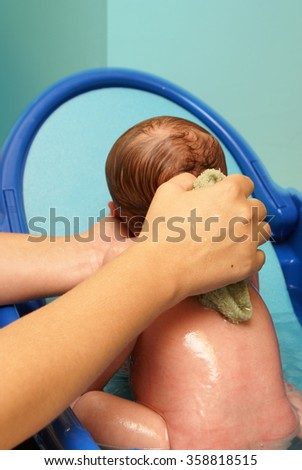 A newborn baby boy is getting his daily scrubbing at home in his infant tub with the tender care of his mother. - stock photo