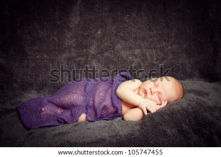 A newborn baby boy is sleeping on a dark background with a blanket. He is wearing a hat. Use it for a childhood, parenting or innocence theme. Soft focus.