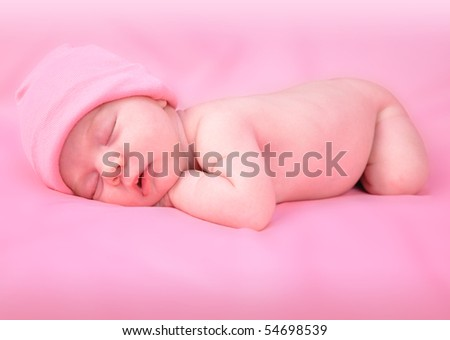 A newborn baby child is laying down on a soft pink isolated background and sleeping with a hat on. The girl is laying belly down. Use the photo to represent life, parenting or childhood. - stock photo