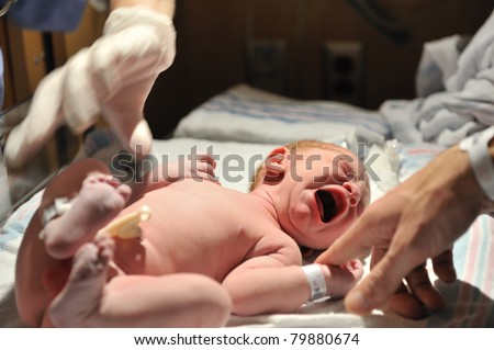 A newborn baby cries moments after birth while dad reaches out to comfort. Has Model Release. - stock photo