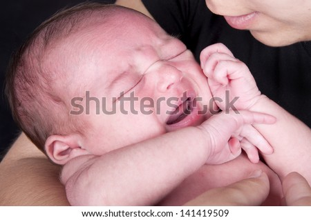 a newborn baby crying held by her mother - stock photo