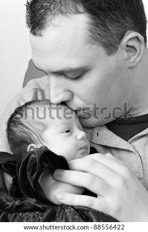 A newborn baby girl being by her dad as he kisses her head in black and white. - stock photo