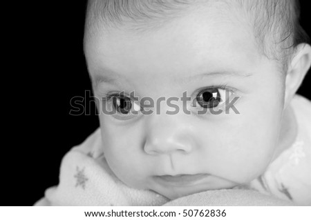 A newborn baby girl in deep though in black and white on a black background