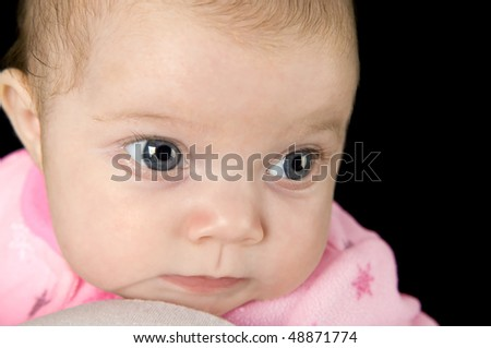 A newborn baby girl in deep though on a black background