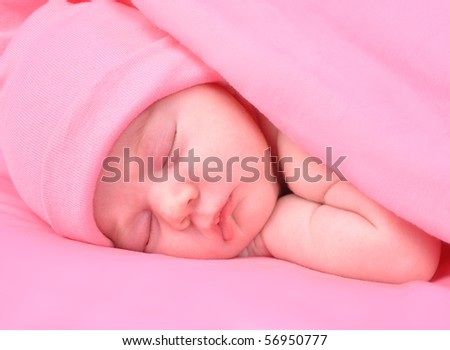 A newborn baby girl is sleeping on a pink background with a blanket. She is wearing a hat. Use it for a childhood, parenting  or innocence theme.