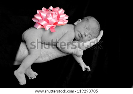 A newborn baby girl wearing a pink bow