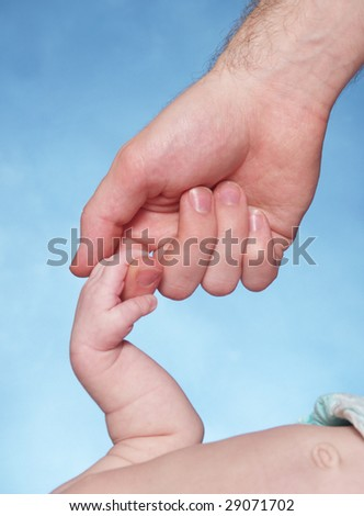 A newborn baby holding her father's hands. - stock photo