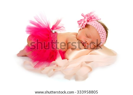 A Newborn Baby in Pink Tutu Dreams about Dance as she sleeps atop Pink Pointe Shoes - stock photo