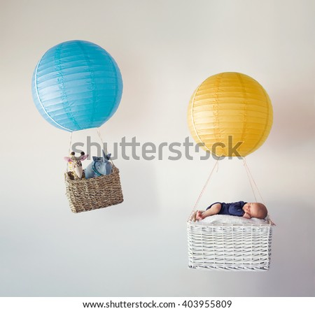 A newborn baby in the basket of an air balloon with his stuffed animal friends  - stock photo