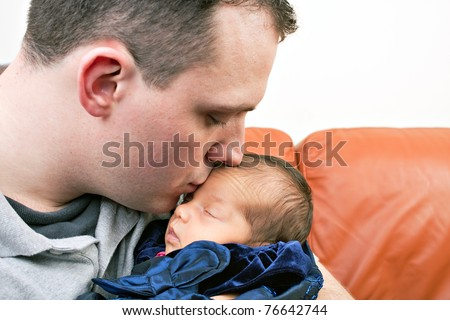 A newborn baby is held by her dad as he kisses her cheek. - stock photo