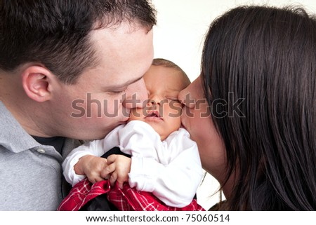 A newborn baby is held by her mother and father as they kiss her cheeks. - stock photo