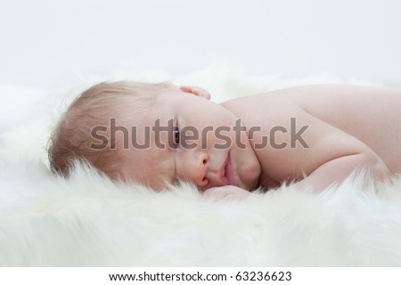 A newborn baby is laying on a soft white fur. - stock photo