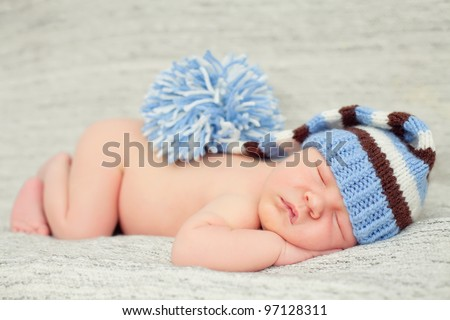 A newborn baby is wearing a blue hat and laying down sleeping on a soft white background. Soft focuss.