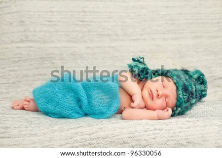 A newborn baby is wearing a blue hat and laying down sleeping on a soft white background. Use the photo to represent life, parenting or childhood.Soft focus, shallow DoF. - stock photo