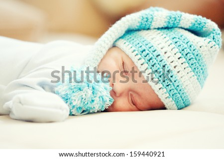 A newborn baby is wearing a blue-white hat and sleeping on a soft  - stock photo
