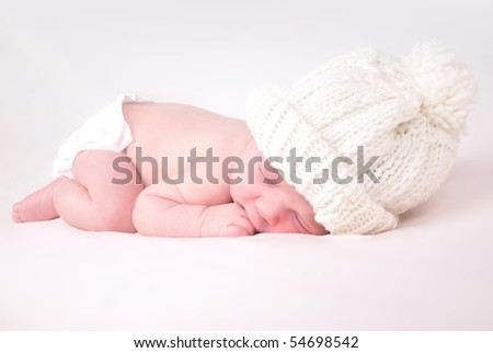 A newborn baby is wearing a white hat and laying down sleeping on a soft white background. Use the photo to represent life, parenting or childhood. - stock photo