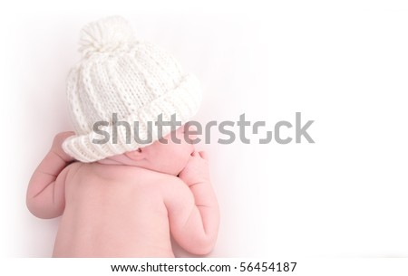 A newborn baby is wearing a white hat and laying down sleeping on a white isolated background. Use the photo to represent life, parenting or childhood.