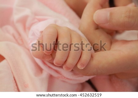 A newborn baby's hand holding the mother's finger.