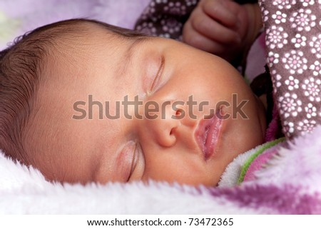 A newborn baby sleeping peacefully under blankets. - stock photo