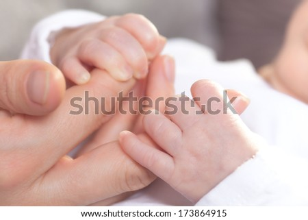 A newborn child is holding the fingers of his father with his little hand. - stock photo