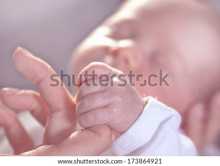 A newborn child is holding the fingers of his mother with his little hand. - stock photo