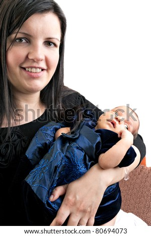 A newborn infant being held in the arms of her smiling mother isolated over a white background. - stock photo