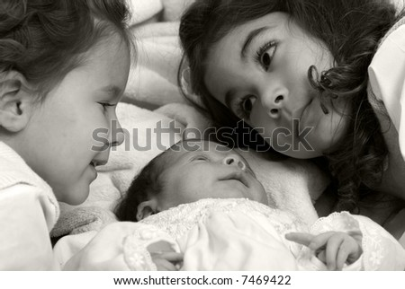 A newborn little girl and her sisters. Family, love, caring. - stock photo