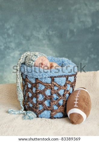 A newborn premature baby boy sleeping in a basket wearing a hat and football, lots of copy space
