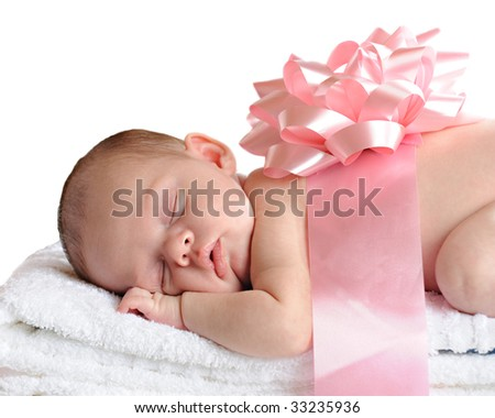 A newborn sleeping on a stack of white towels and wrapped in a big, pink bow.  Isolated on white. - stock photo