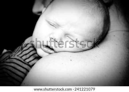 A Newborn Sleeps in his Mother's Arms - stock photo