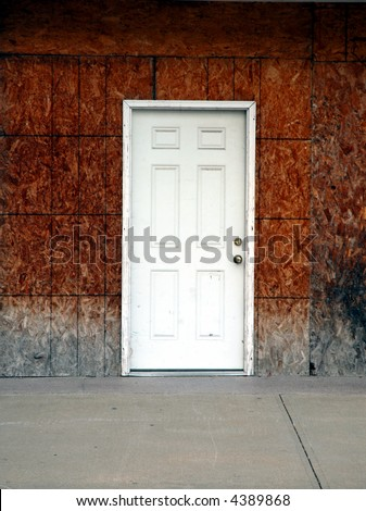 A newer white door leads into an old dilapidated building without siding. - stock photo